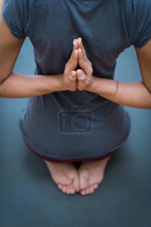 Women practicing yoga: reverse prayer pose