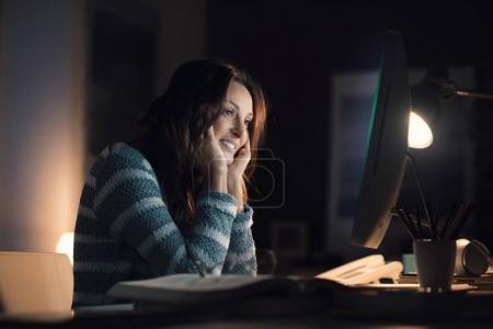 Foto de Feliz sonriente a mujer relajante en casa y la conexión con su ordenador, ella está viendo videos en línea - Imagen libre de derechos