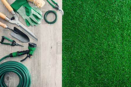 Photo for Gardening tools on a wooden table and lush grass, hobby and garden manteinance concept - Royalty Free Image