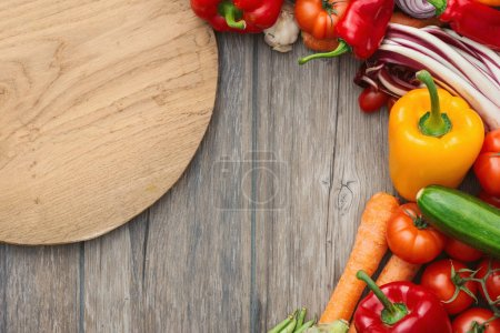 Photo for Fresh tasty vegetables and vintage chopping board on a rustic wooden worktop, cooking and vegetarian recipes concept - Royalty Free Image