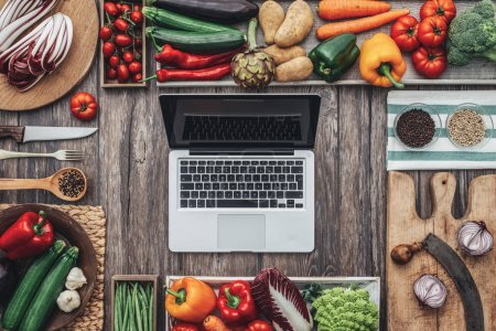 Photo for Fresh healthy vegetables, chopping boards and cooking utensils composing a frame on a vintage kitchen worktop, laptop at center - Royalty Free Image