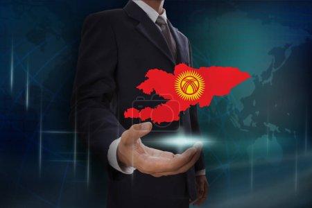 Photo pour Homme d'affaires montrant la carte et le drapeau du Kirghizistan sur fond de globe - image libre de droit