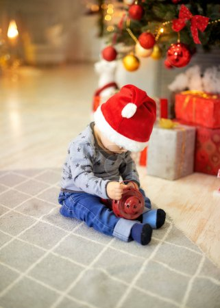 little boy sitting on a background of christmas tree
