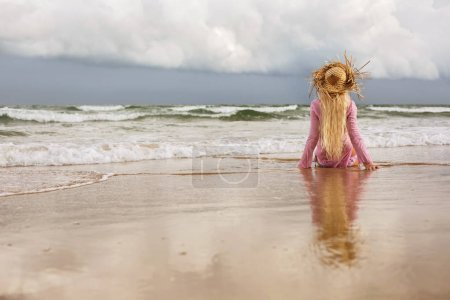 Photo for Blond woman sitting on sea shore, enjoy viewing ocean waves and beautiful clouds. Relax, freedom, summer vacation - Royalty Free Image