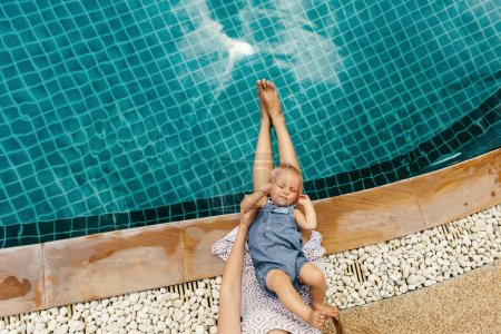 baby boy laying on mother legs near pool