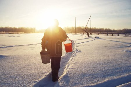 Winter Village. Man walking with buckets for water to the well on the snow drifts. Life in Russian village in cold winter