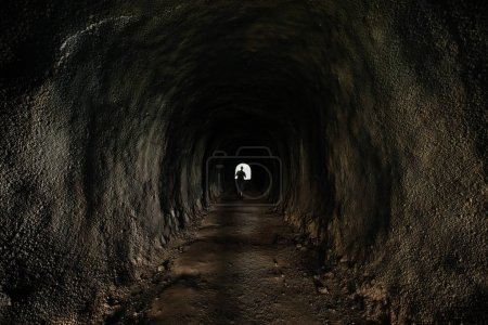 Photo for Man silhouette in dark cave tunnel - Royalty Free Image