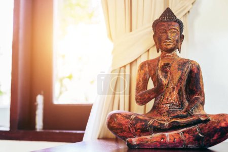 Photo for Living room interior decor: buddha statue on the table near the window - Royalty Free Image