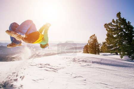 acrobatic guy jumping somersault on snow