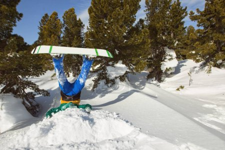 Snowboarder upside down in snow