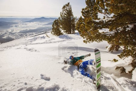 Snowboarder lying down in snow