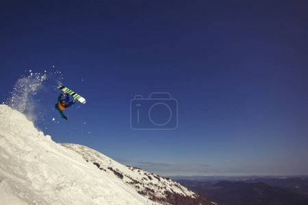 Snowboarder jumping upside down