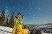 Female snowboarder playing with snow