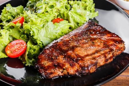 gegrilltes Steakfleisch mit frischem Gemüsesalat und Tomaten auf schwarzem Teller, Holzhintergrund