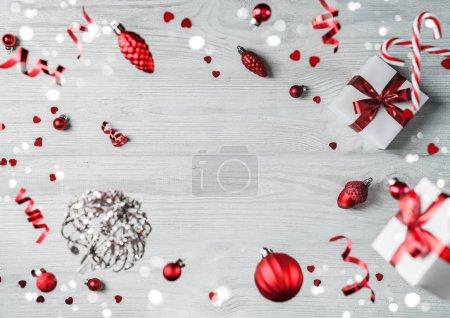 Foto de Feliz Navidad y Año Nuevo. Tarjeta de vacaciones Xmas hecha de decoraciones voladoras, ramas de abeto, bolas rojas, copas de nieve, chispas, bokeh, luz sobre fondo de madera. Enfoque selectivo - Imagen libre de derechos