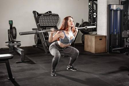 Attractive fit woman works out with dumbbells as a fitness conceptual over gray gym background.