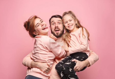 Happy young family with one little daughter posing together