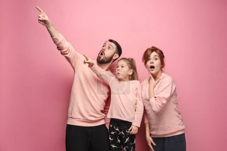 Surprised young family on pink