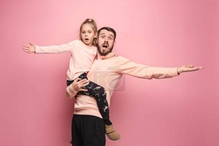 cheerful father playing with daughter on pink
