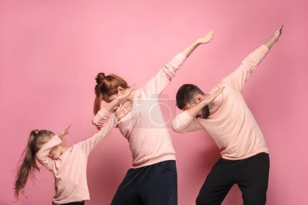 The dancing young family on pink