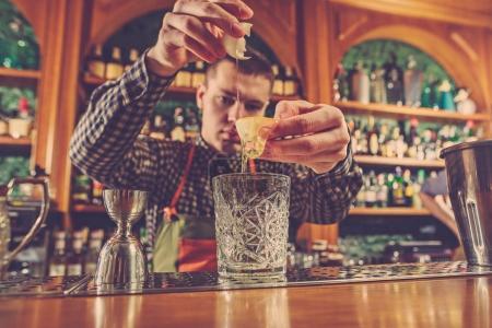 Photo pour Le barman préparant un cocktail alcoolisé au comptoir du bar sur le fond du bar - image libre de droit