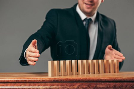 Photo for Man and wooden cubes on table. Management and marketing concepts - Royalty Free Image