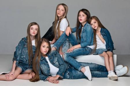 Photo pour Le groupe de filles assis ensemble et se présentant à la caméra. Portrait en studio d'adolescentes caucasien de mode séduisante jeune habillée en jeans regroupés. Vue de face - image libre de droit