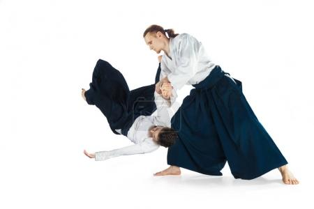 Photo for Man and woman fighting at Aikido training in martial arts school. Healthy lifestyle and sports concept. Man with beard in white kimono on white background. Karate woman with concentrated face in - Royalty Free Image