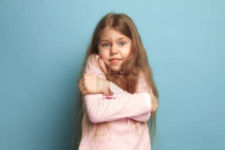 Photo pour La surprise. La jeune fille surprise sur un fond bleu studio. Les expressions faciales et les émotions des gens concept. Des couleurs tendance. Vue de face. Portrait à mi-longueur - image libre de droit