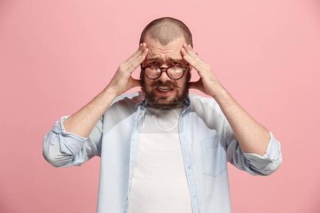 Photo pour Un homme a mal à la tête. Isolé sur fond rose. Homme d'affaires debout avec douleur isolé sur fond studio rose tendance. Portrait masculin mi-long. Émotions humaines, concept d'expression faciale. Avant - image libre de droit