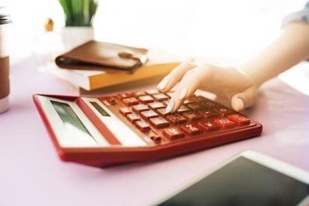 Photo pour Femme tient sac à main, carte de crédit dans les mains et le calcul des coûts. Table rose. Des fleurs sur la table. main tenant sac brun. Calcul rouge . - image libre de droit