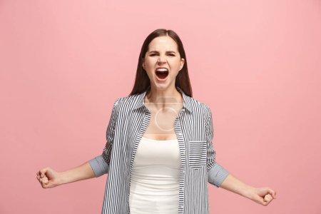 Photo pour Crier, haine, rage. Pleurs émotionnelle femme en colère criant sur fond de studio rose. Émotionnels, jeune visage. Female portrait demi-longueur. Émotions humaines, notion de l'expression du visage. Couleurs tendances - image libre de droit