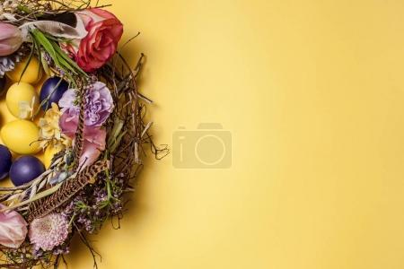 Photo pour Carte de Pâques. Œufs de Pâques peints dans le nid sur fond de table jaune. Vue de dessus de la décoration de Pâques. Joyeux concept de Pâques. Couleurs tendance - image libre de droit