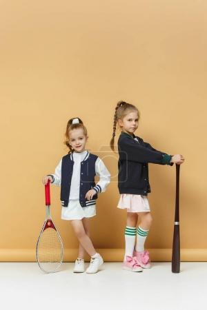 Foto de Retrato de dos niñas como jugadores de béisbol y tenis con raqueta de tenis, poco. Estudio de disparo. Fondo pastel. Estilo adolescentes niñas posando en el estudio. Estilo deportivo. Moda deportiva de niños y adolescentes - Imagen libre de derechos