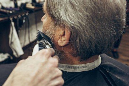 Photo pour Côté gros plan arrière principal beau barbu homme caucasien se barbe toilettage en salon de coiffure moderne. Client de desserte coiffeur, faire la coupe de cheveux barbe à l'aide de la machine à raser. Barber shop concept. - image libre de droit