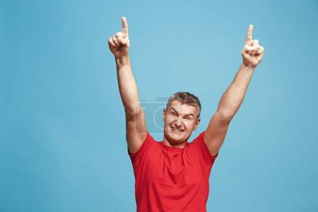 Photo pour J'ai gagné. Gagner le succès homme heureux célébrant être un gagnant. Image dynamique du modèle masculin caucasien sur fond de studio bleu. Victoire, concept de délice. Concept d'émotions faciales humaines. Couleurs tendance - image libre de droit