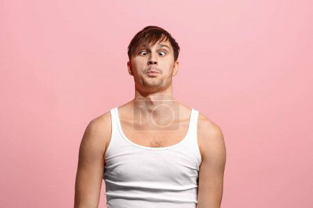 Photo for I lost my mind. The squint eyed man with weird expression. Beautiful male half-length portrait isolated on pink studio backgroud. The crazy man. The human emotions, facial expression concept. - Royalty Free Image