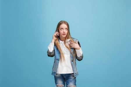 Photo for Wow. Beautiful female half-length front portrait isolated on blue studio backgroud. Young emotional surprised teen girl standing with mobile phone. Human emotions, facial expression concept. Trendy - Royalty Free Image