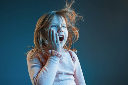 Photo for The anger and surprised teen girl. Hate, rage. Crying emotional angry teenager in colorful bright lights at studio background. Emotional face. Sport fan human emotions, facial expression concept. - Royalty Free Image
