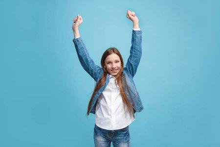 Photo pour J'ai gagné. Gagner le succès heureuse adolescente célébrant être un gagnant. Image dynamique du modèle féminin caucasien sur fond de studio bleu. Victoire, concept de délice. Concept d'émotions faciales humaines. Tendance - image libre de droit
