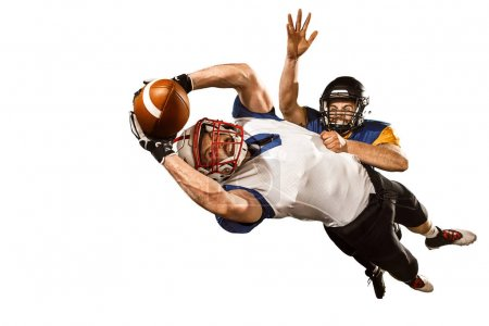 Photo for Active two american football player isolated on white background. Fit caucasian men in uniform with ball jumping over studio background in jump or motion. Human emotions and facial expressions concept - Royalty Free Image