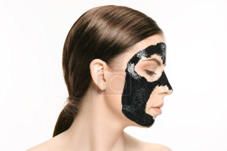 Photo pour Jeune femme belle caucasienne appliquant un masque noir cosmétique pour le visage de la boue noire thérapeutique. Concept beauté Spa traitement et le visage. Soins du visage féminin et les concepts de la peau parfaite - image libre de droit