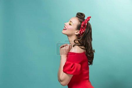 Photo pour Le profil de jeune femme avec pin up maquillage et coiffure au studio. Heureux, souriant et assez féminin modèle caucasien dans un style rétro ou vintage. Concept de pin-up. Les émotions humaines et les expressions faciales - image libre de droit