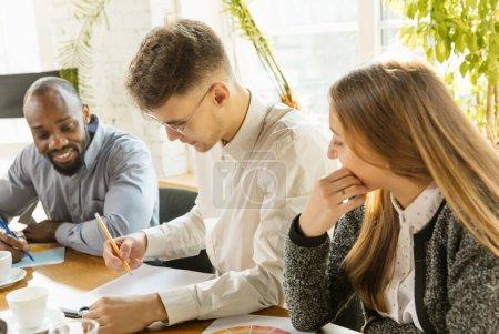 Photo pour Groupe de jeunes professionnels des affaires en réunion. Divers groupes de collègues discutent de nouvelles décisions, de plans et de stratégies futurs. Réunion créative et lieu de travail, entreprise, finance, travail d'équipe . - image libre de droit