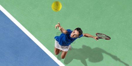 Photo pour Jeune femme brune caucasienne en chemise bleue jouant au tennis au court. Frappe balle avec raquette, à l'extérieur. Jeunesse, flexibilité, puissance, énergie. Copyspace. Vue de dessus. Mouvement, action, mode de vie sain . - image libre de droit