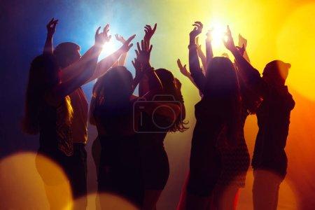 Photo pour Des rêves. Une foule de personnes en silhouette lève les mains sur la piste de danse sur fond clair néon. Vie nocturne, club, musique, danse, mouvement, jeunesse. Couleurs jaune-bleu et filles et garçons en mouvement . - image libre de droit