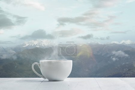 Photo for Single tea or coffee mug and landscape of mountains on background. Cup of hot drink with snowly look and cloudly sky in front of it. Warm in winter day, holidays, travel, New Year and Christmas time. - Royalty Free Image