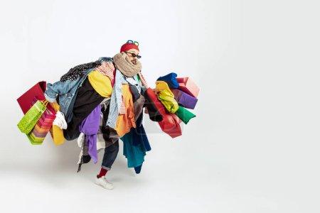 Photo pour Faire du shopping comme un problème. Un homme accro aux ventes. Surproduction et demande insensée. Modèle féminin portant trop de vêtements colorés, besoin de plus. Mode, style, vendredi noir, vente, achats abusifs - image libre de droit