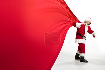 Photo for Santa Claus pulling huge bag full of christmas presents isolated on white background. Caucasian male model in traditional costume. New Year 2020, gifts, holidays, winter mood. Copyspace for your ad. - Royalty Free Image