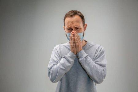 Photo pour Je ne peux pas respirer. L'homme caucasien portant le masque de protection respiratoire contre la pollution atmosphérique et les particules de poussière dépasse les limites de sécurité. Santé, environnement, concept d'écologie. Allergie, maux de tête . - image libre de droit